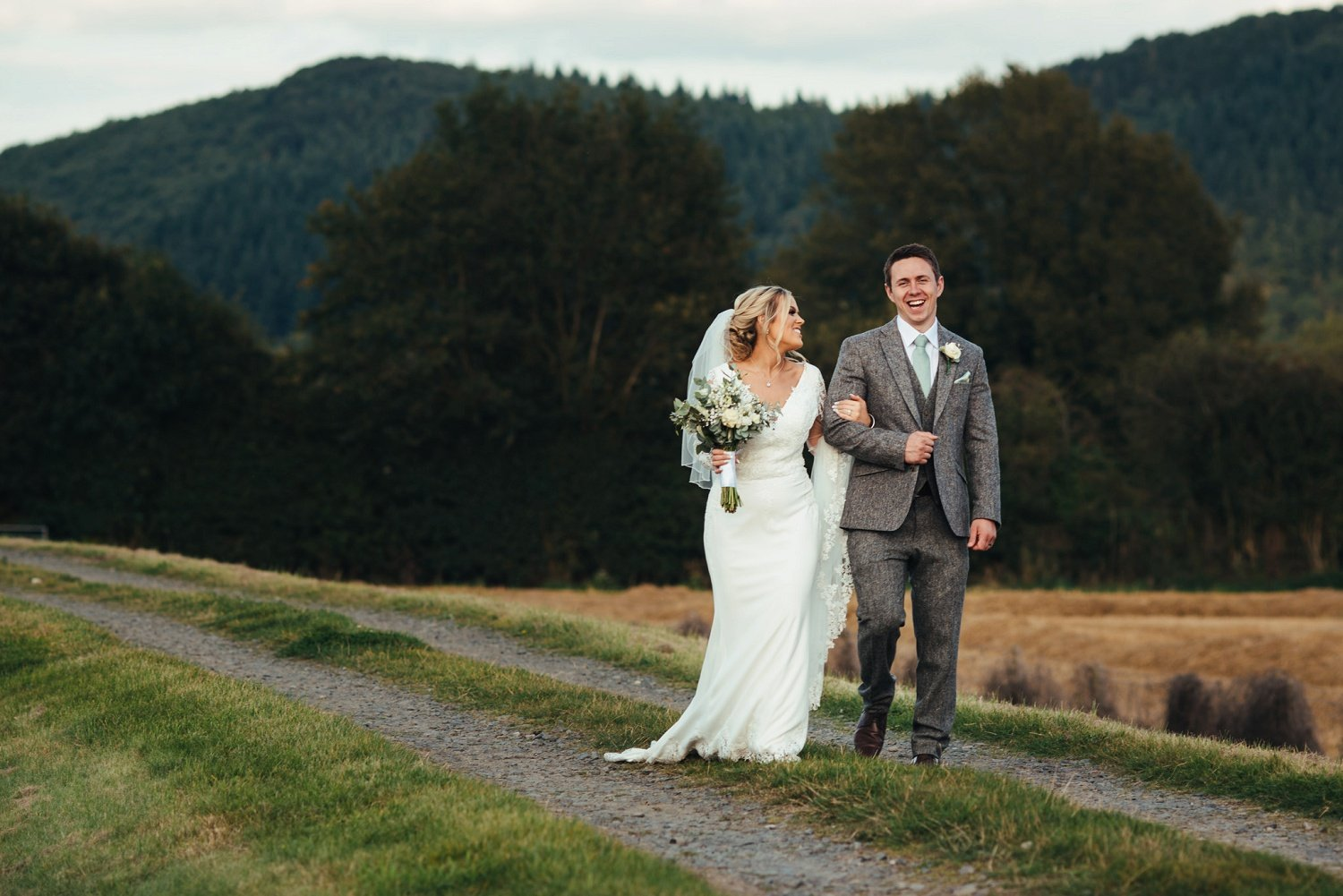 Happy bride and groom walk together on the path along the river Wye at Redbank in Herefordshire