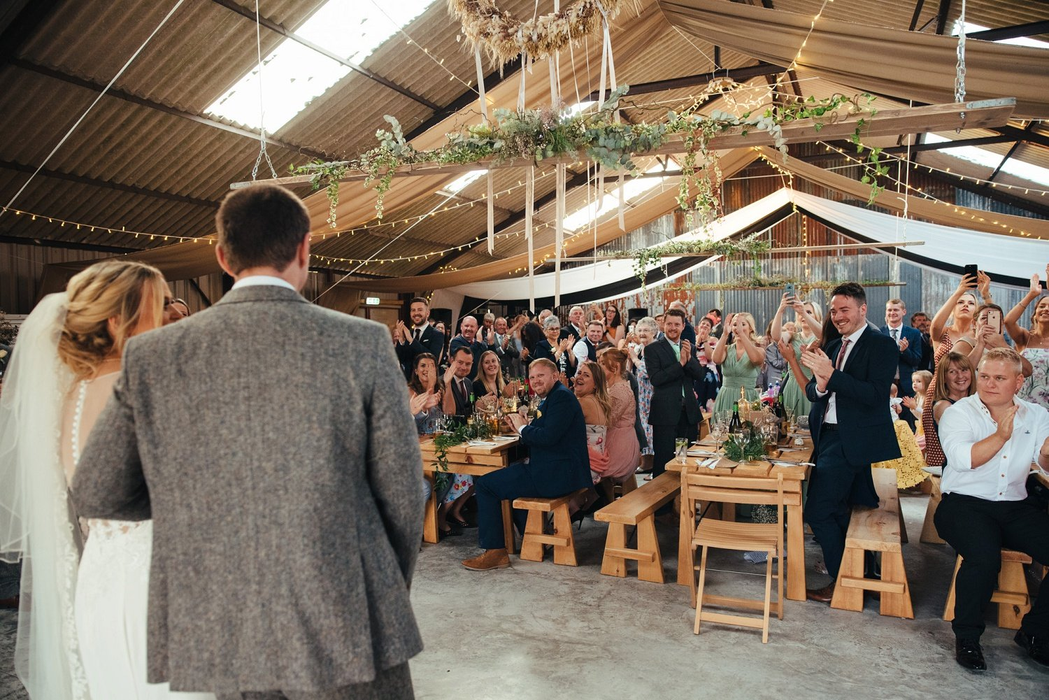 Wedding guests welcome the bride and groom inside the Barn at Redbank in Herefordshire