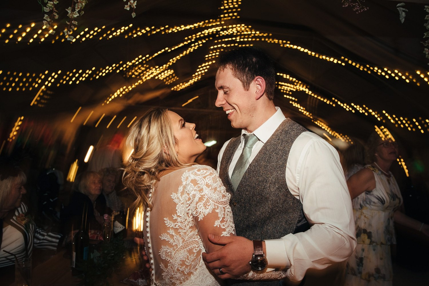 Bride and groom dance together under the fairy lights at Redbank barn in Herefordshire