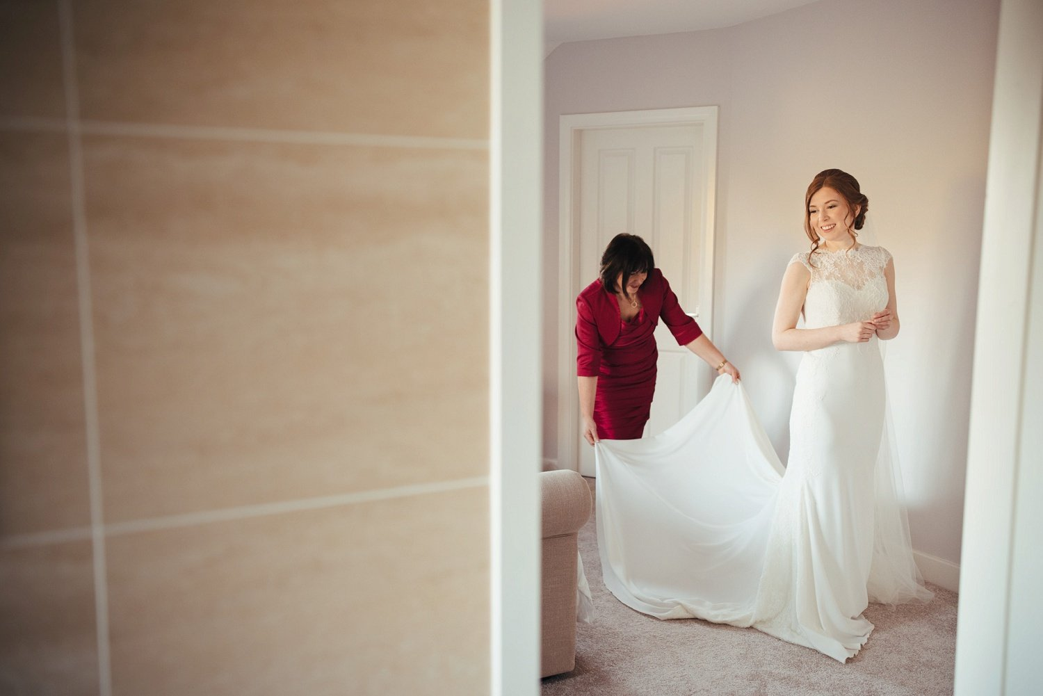 Mother of the bride arranges wedding dress train for a dress from Hagley Bridal Studio