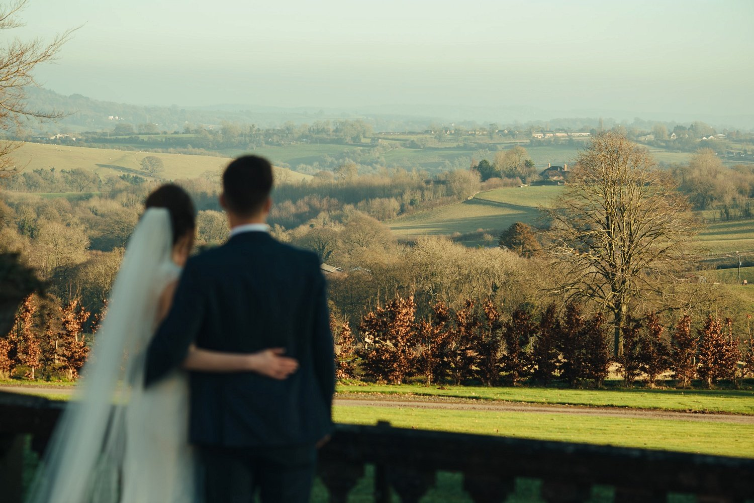 Bride and groom looking out into the distance admiring the wast views rfom Bredenbury Court Barns in Herefordshire