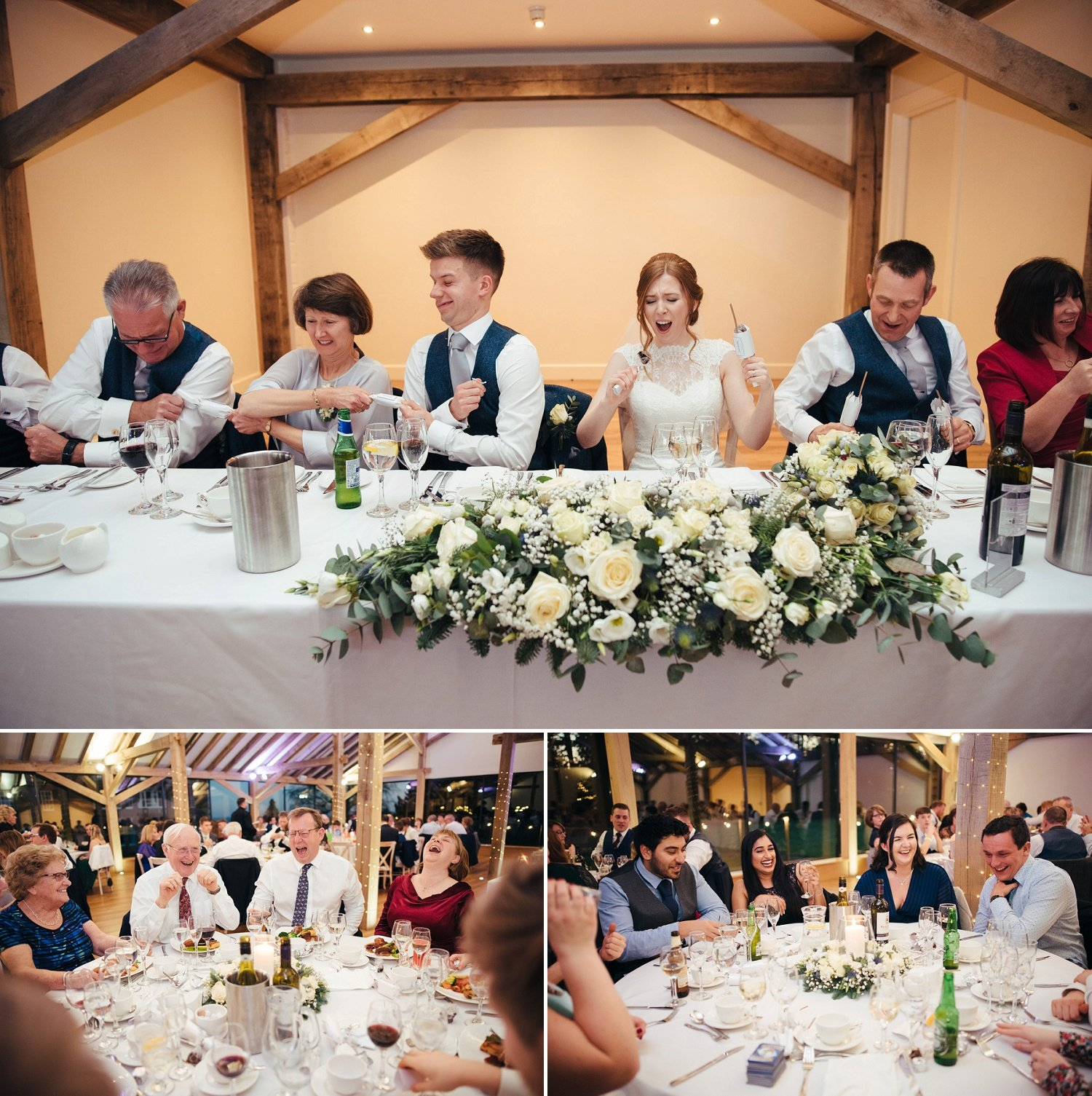 Crackers are pulled with a bang by the top table at a late December wedding at Bredenbury Court Barns