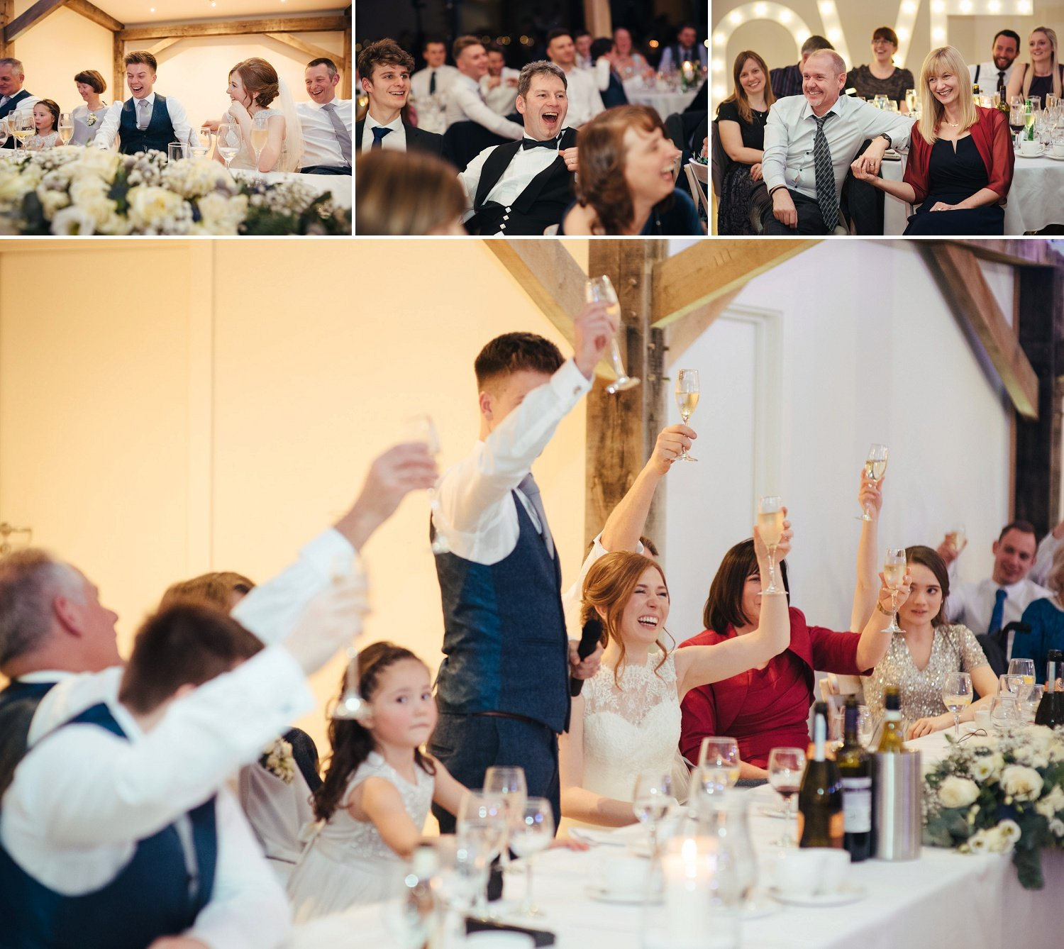 Entire top table toasting for the bride and groom at a contemporary barn wedding venue in Herefordshire