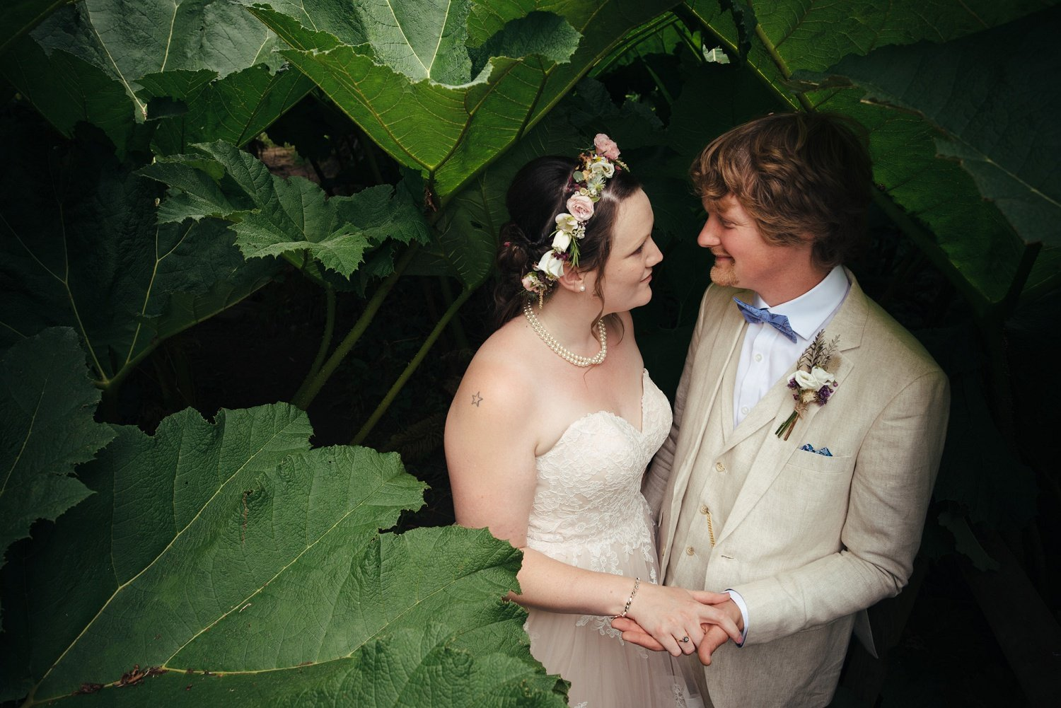 Half body photo of a bride and groom looking at each other in the follies