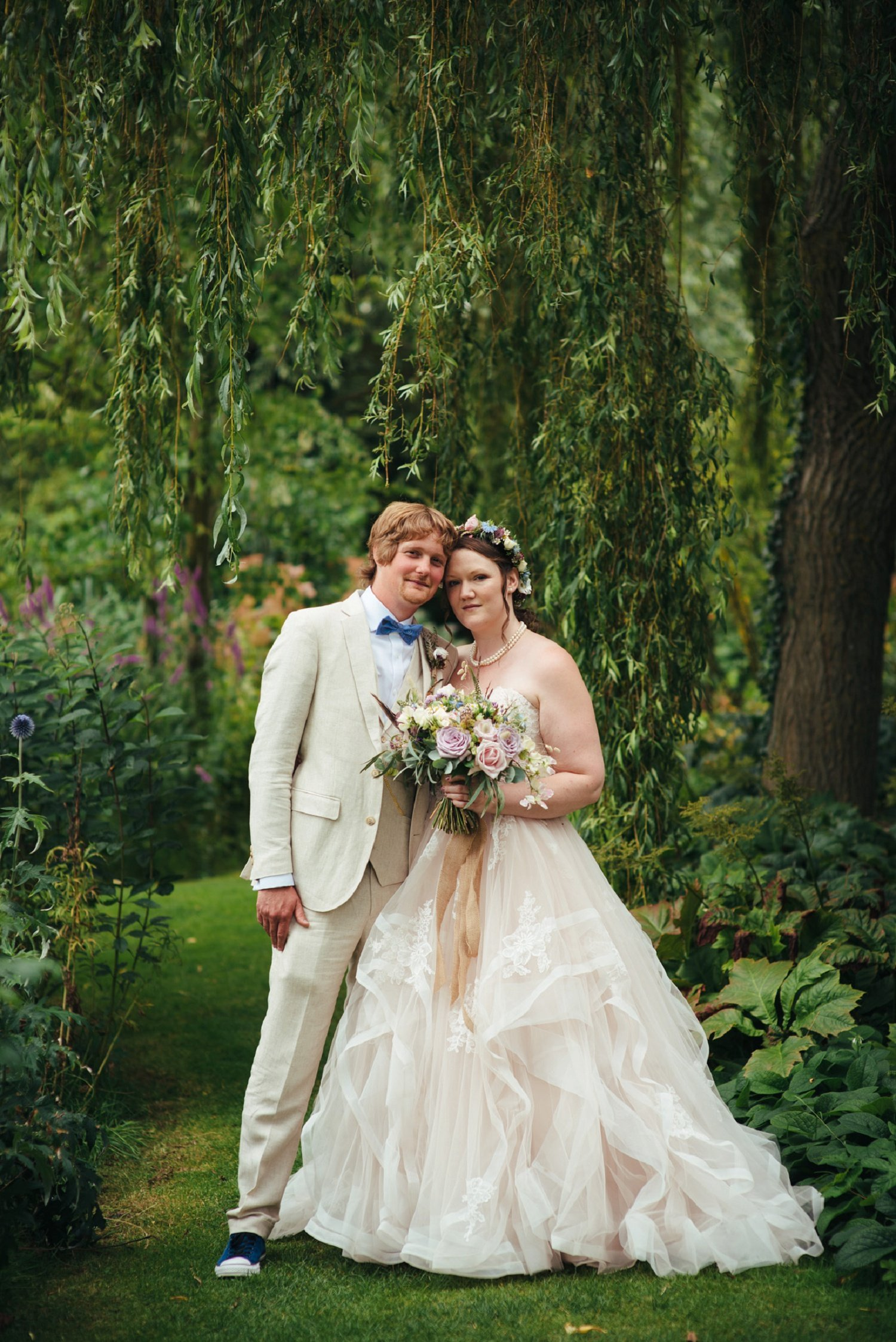 Bride and groom full body portrait at Westonbury Mill Water Gardens, in front of a weeping tree
