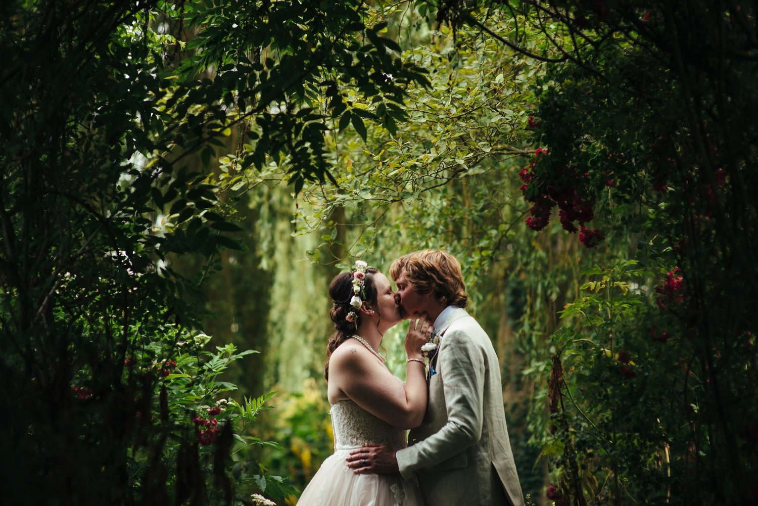 Bride and groom kidding surrounded by lots of greenery at Westonbury Mill Water Gardens
