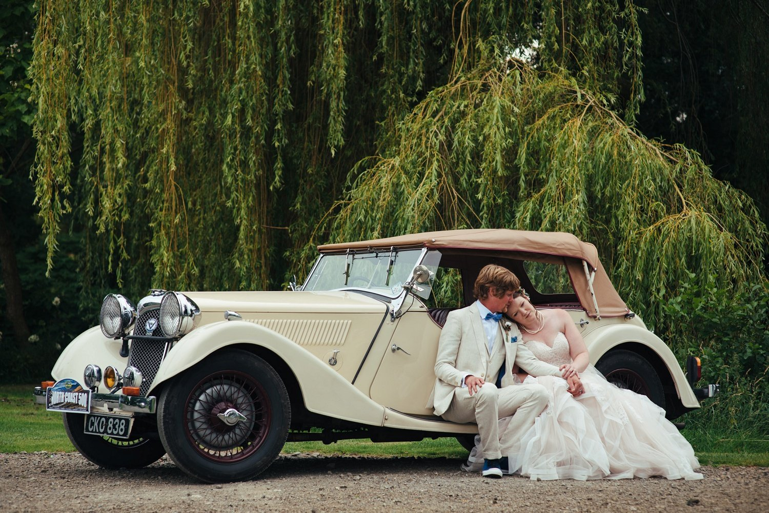 Bride and groom sitting down on a vintage car at Westonbury Mill Water Gardens