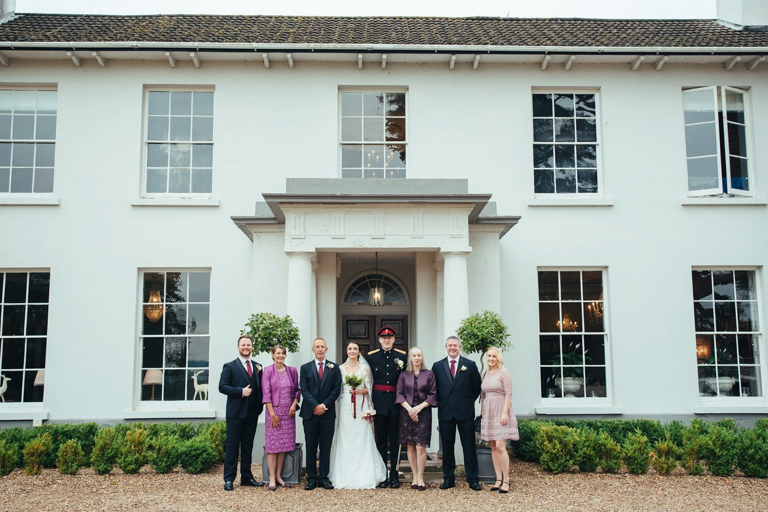 Photo of bride and groom with both sets of parents at Glewstone Court in Herefordshire