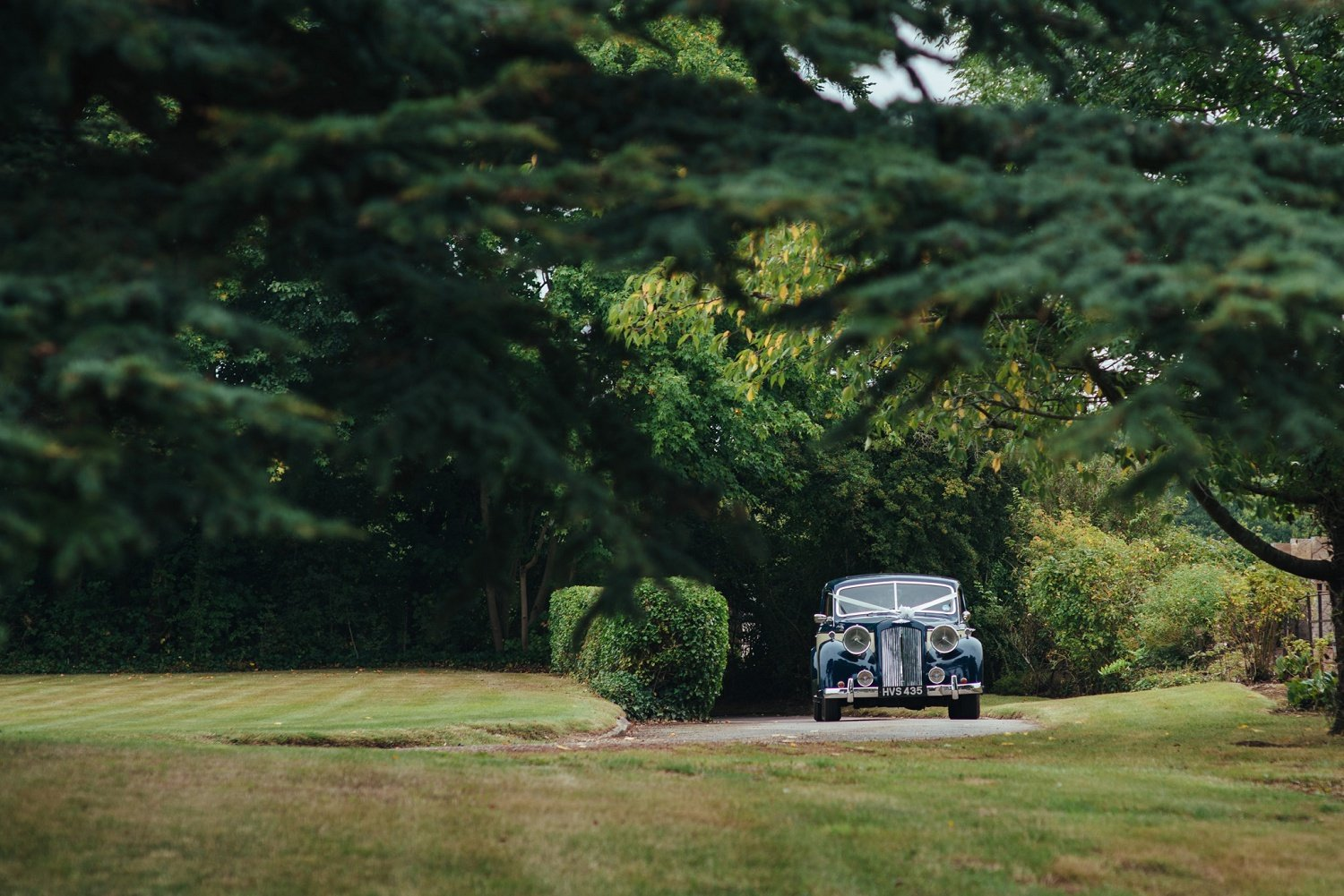 Bride arrives in a blue vintage austin from Nostalgia wedding cars