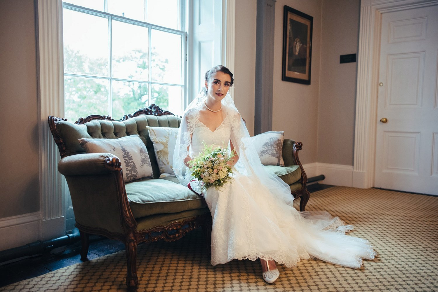 Bride portrait on vintage sofa at Glewstone Court