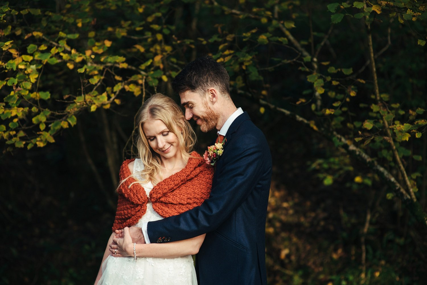 Boho bride wearing a teracotta knitted shawl enjoys being in her groom's arms