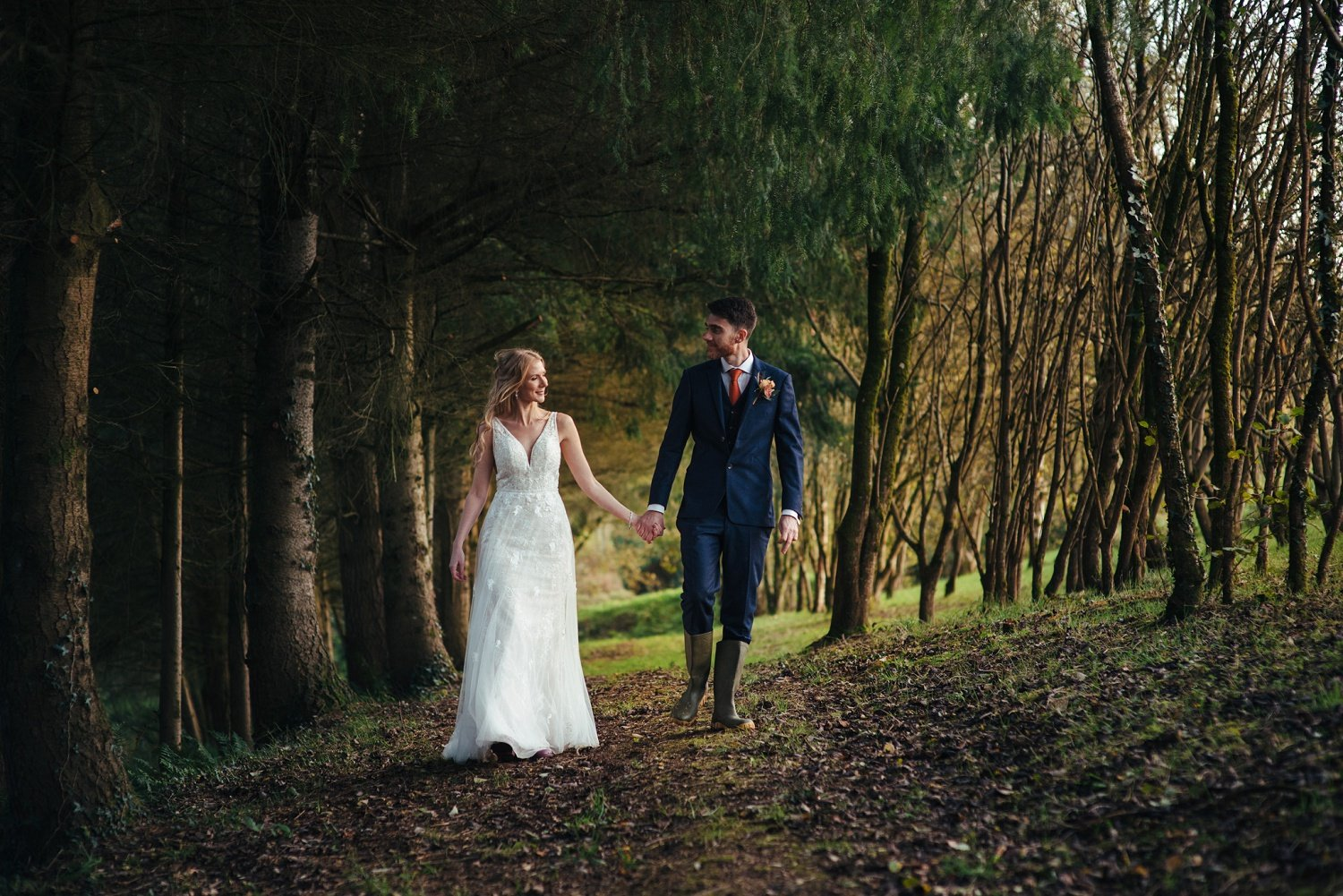 Brie and groom walk hand in hand on a forest path in the golden evening sunlight at Tree Top Escape, Devon