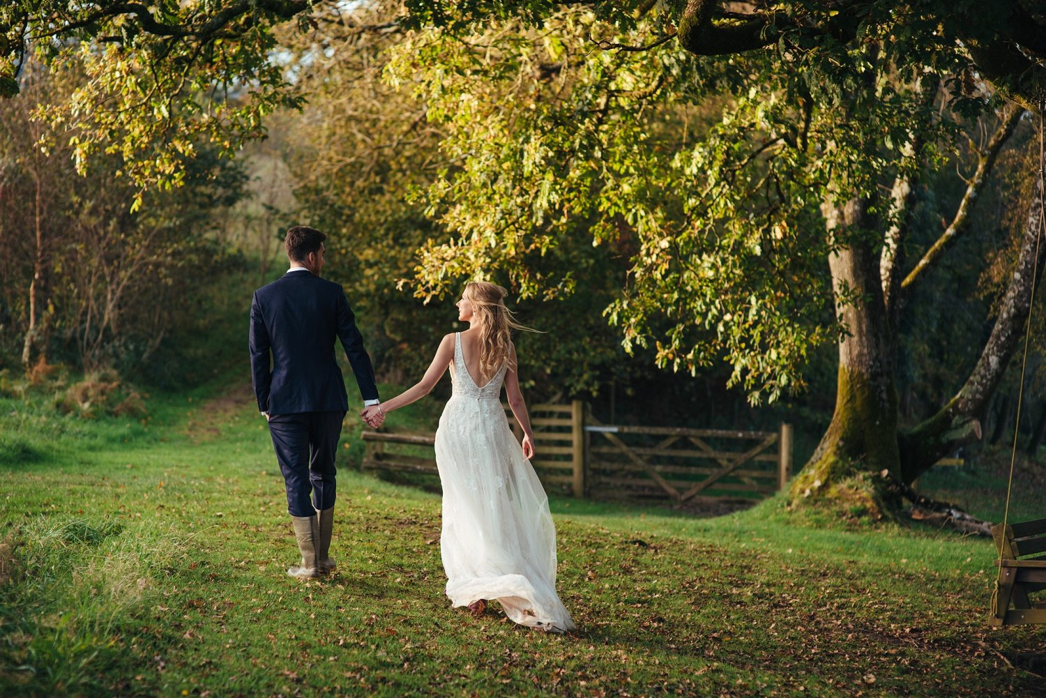 Bride wearing bohemian wedding dress follows her groom towards a clearing in the forest