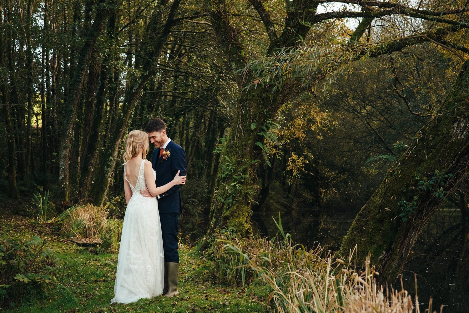 Bohemian flowy wedding dress and a beautiful blonde bride in her groom's arms by a lake