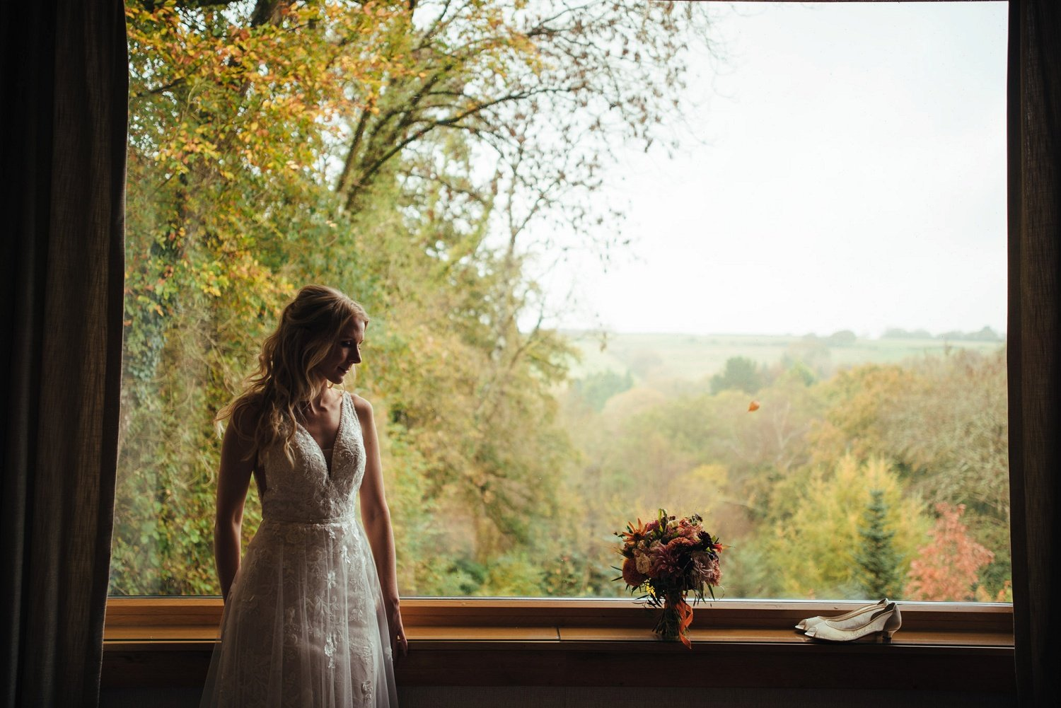 Portrait of bride by a huge window with glorious autumnal views over a valley in Devon, UK