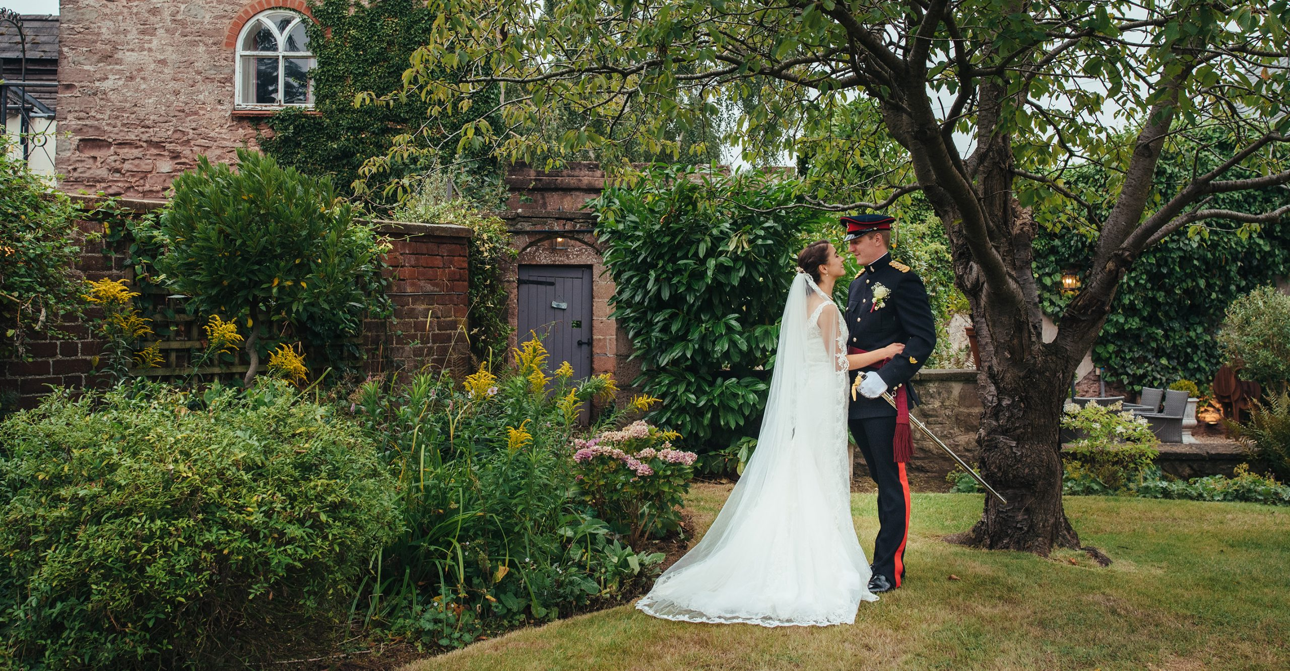 Bride and groom photo in the beautiful summer gardens at Glewstone Court