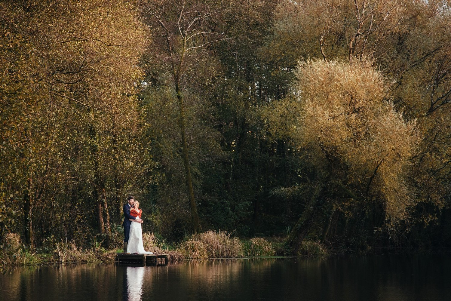 Bride and groom autumnal photo by the lake at Tree Top Escape, Devon